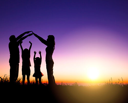 Family at sunset who are raising arms to make house silhouette